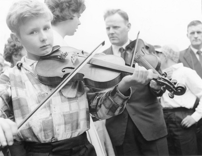 Young boy and man playing fiddle at the Fleadh Cheoil, Gorey, 1962 / Bord Fáilte