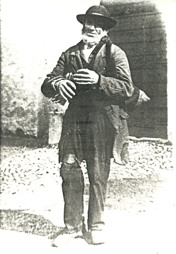Unidentified piper standing on street / [unidentified photographer]