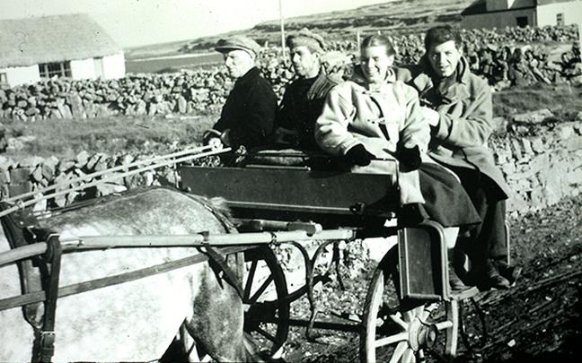 Jean Ritchie and George Pickow with Beairtlín Bhaba Ó hIarnáin and Peaitsín Ó Fátharta, with the Man of Aran cottage in the background, Cill Mhuirbhigh, Árainn, 1952, courtesy of Prof. Dáibhí Ó Cróinín / [unidentified photographer]