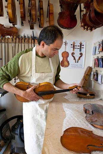 Fiddle maker Kuros Torkzadeh's holding the body of a fiddle / Stephen Power