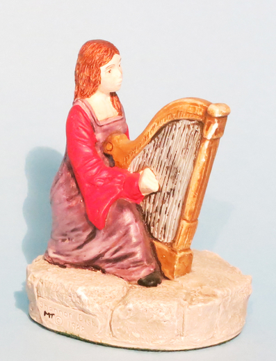 Ceramic girl playing harp / ITMA photographer