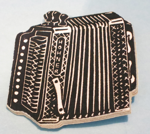 Badge featuring a melodeon / ITMA photographer