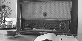 Grayscale Photography Of Transistor Radio On Table Near Opened Book And Eyeglasses Thumbnail