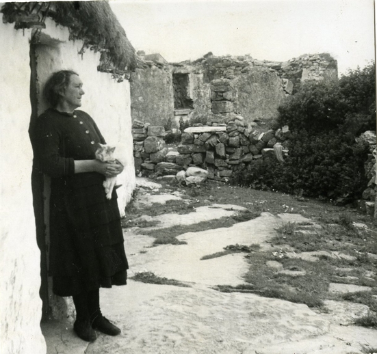 Maggie Dirrane (1899-1995) at her back door in Eoghanacht, Árainn, August 1956, courtesy of the Ralph Rinzler Folklife Archives and Collections / Sidney Robertson Cowell