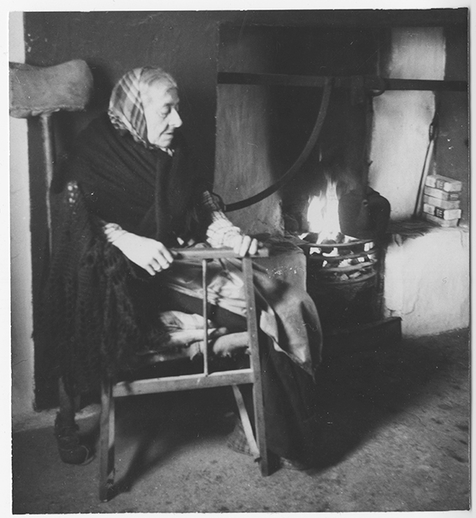 Bríd Iarnáin (1869-1965) by her fireside, Sruthán, Árainn, August 1956. She broke her hip some years before and her crutch can be seen behind her chair. Courtesy of the Ralph Rinzler Folklife Archives and Collections / Sidney Robertson Cowell